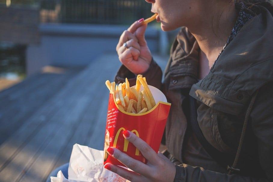Une femme mange du Mc Donald